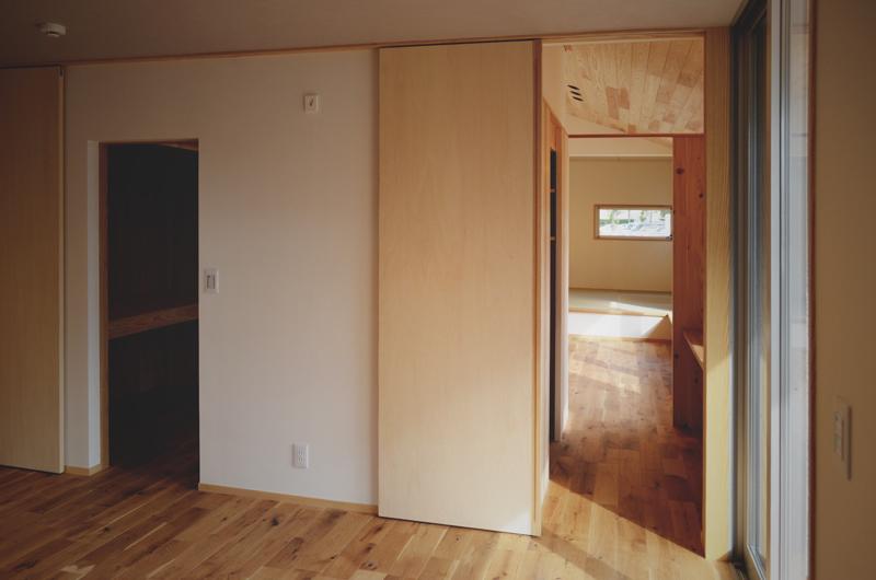 天井いっぱいの木製引き戸の寝室兼子供部屋